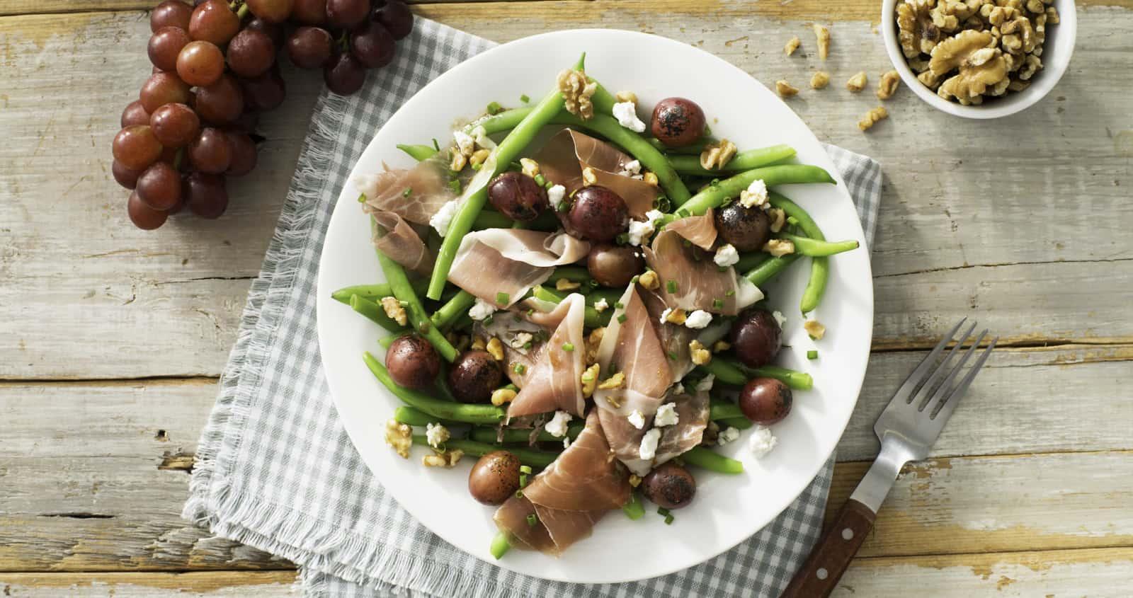 Salade de haricots verts, de prosciutto et de fromage de chèvre garnie de raisins grillés